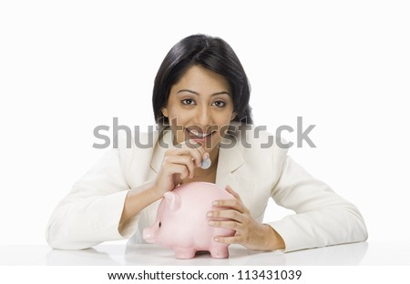 Businesswoman inserting a coin into a piggy bank - stock photo