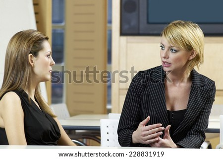 Businesswoman instructing another businesswoman in office setting - stock photo