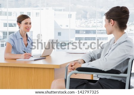 Businesswoman interviewing disabled candidate at desk in office - stock photo