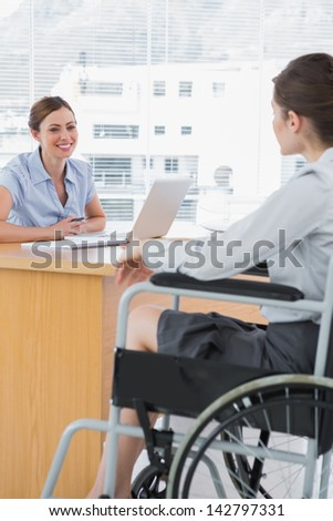 Businesswoman interviewing disabled job candidate in her office and smiling - stock photo