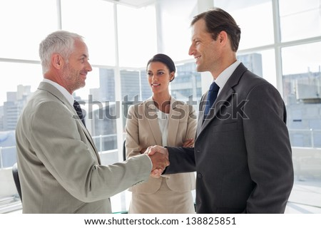 Businesswoman introducing colleagues together in their office - stock photo