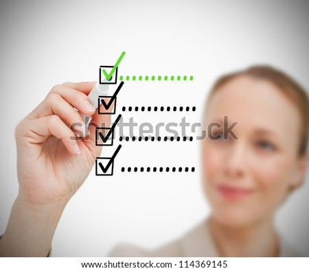 Businesswoman is drawing a tick while smiling - stock photo