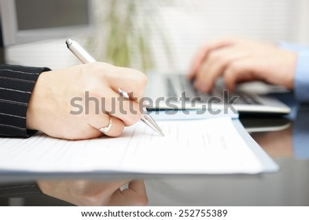 businesswoman is filling contract and businessman is typing on computer in background - stock photo