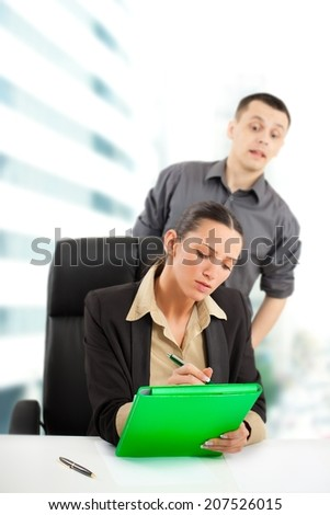 Businesswoman is hard working while her colleague looking furtively what she is writing. - stock photo