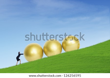 Businesswoman is pushing three golden eggs on top of green hill - stock photo