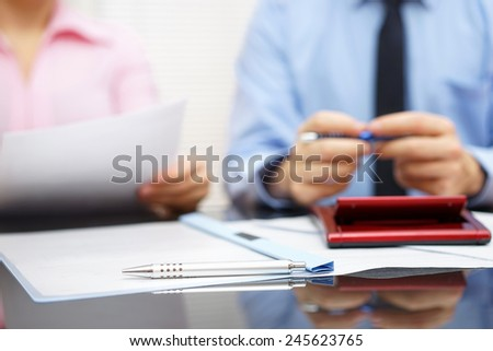 businesswoman is reading contract to businessman in blur background, focus is on pen - stock photo