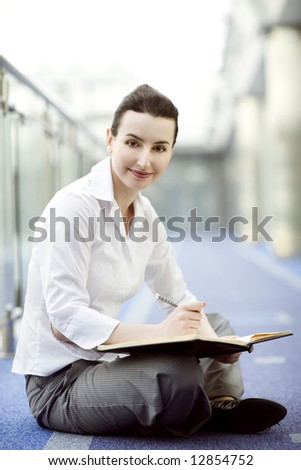 Businesswoman is sitting on the floor with a calendar on hewr lap - stock photo