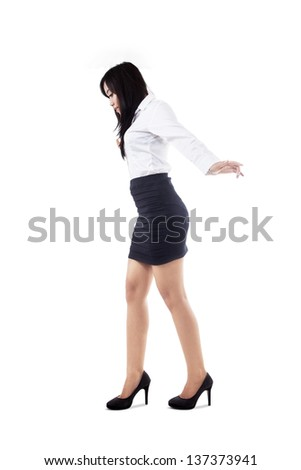Businesswoman is trying to get  balance by standing on copyspace, isolated on white - stock photo