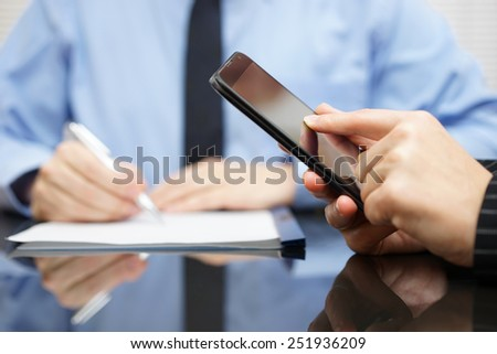 businesswoman is using mobile smart phone and businessman in background is writing on document