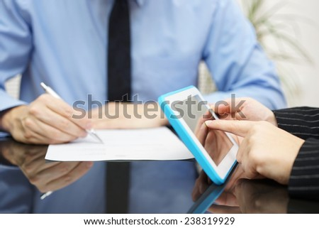 businesswoman is working with tablet pc and businessman is writing a document - stock photo