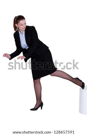 Businesswoman kicking a stool - stock photo