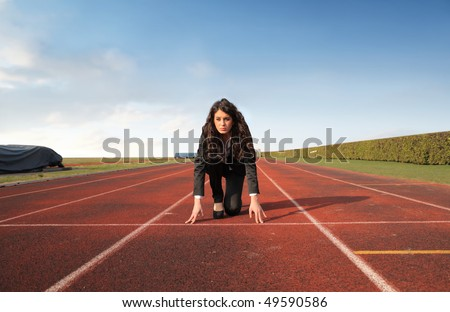 Businesswoman kneeling on the starting grid of a running track - stock photo