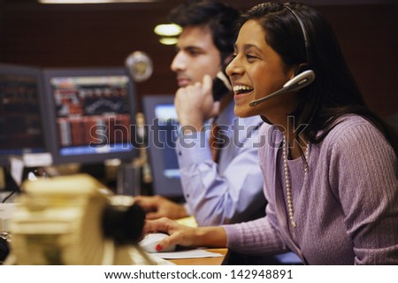 Businesswoman laughing while talking on a headset - stock photo
