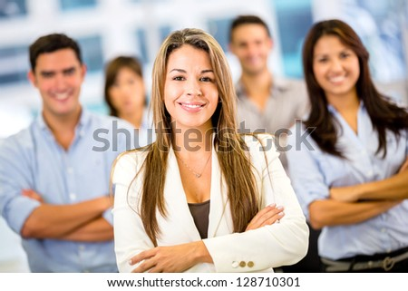Businesswoman leading a business group and looking happy - stock photo