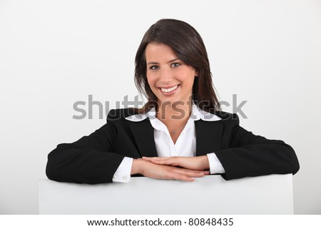 Businesswoman leaning on a board left blank for your message - stock photo