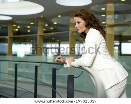 Businesswoman leaning on handrail - stock photo