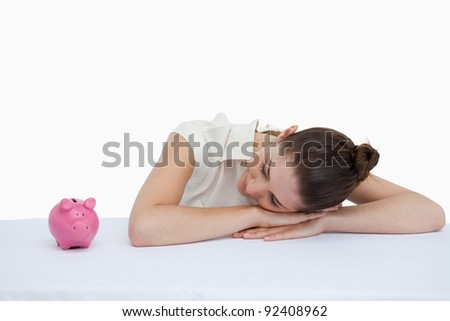 Businesswoman leaning on her desk looking at a piggy bank against a white background - stock photo