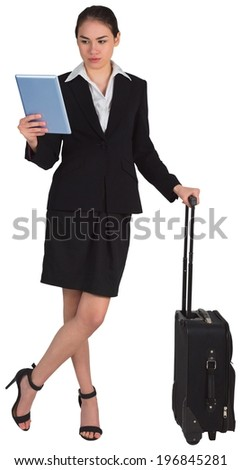 Businesswoman leaning on her suitcase holding tablet pc on white background