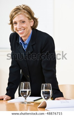 Businesswoman leaning on table - stock photo