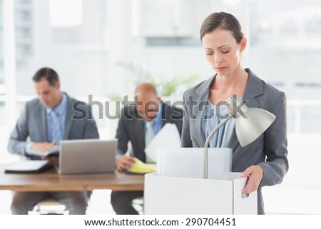 Businesswoman leaving office after being fired and carrying her belongings - stock photo