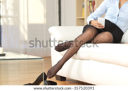 Businesswoman legs with nylons resting after work texting on a mobile phone - stock photo