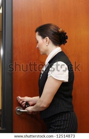 Businesswoman locking a door. - stock photo