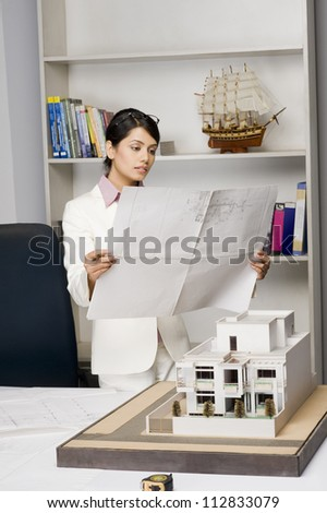 Businesswoman looking at a blueprint in an office - stock photo