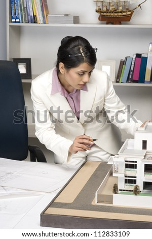 Businesswoman looking at a model home in an office - stock photo