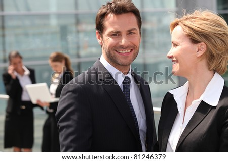 Businesswoman looking at businessman smiling - stock photo