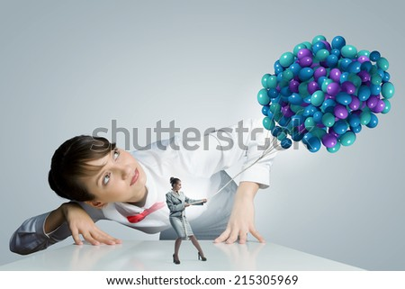 Businesswoman looking at businesswoman miniature pulling bunch of balloons - stock photo
