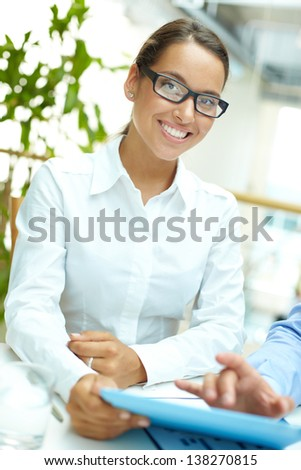 Businesswoman looking at camera at meeting with colleague - stock photo