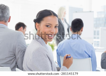 Businesswoman looking at camera during meeting in meeting room - stock photo