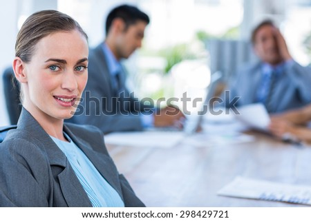 Businesswoman looking at camera while her colleague working in office - stock photo