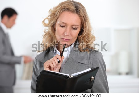 Businesswoman looking at diary - stock photo