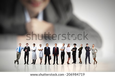 Businesswoman looking at group of businesspeople in miniature