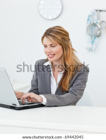 Businesswoman looking at her laptop at home - stock photo