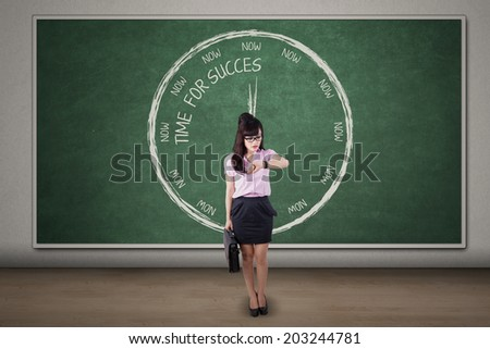 Businesswoman looking at her watch symbolizing Time for Success - stock photo