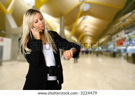 Businesswoman looking at her watch while being on the phone, standing in the departure hall of an airport, waiting to catch her flight for her business travel. - stock photo