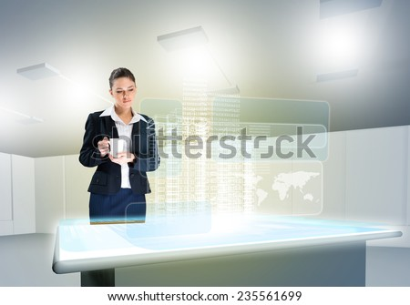 Businesswoman looking at hologram of construction project - stock photo
