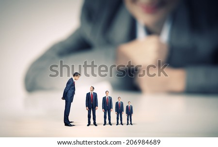 Businesswoman looking at miniature of business people of different sizes - stock photo