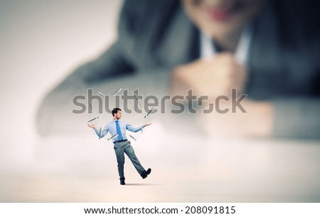 Businesswoman looking at miniature of man juggling with items - stock photo