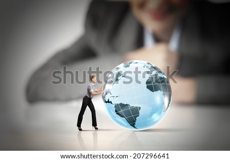 Businesswoman looking at miniature of woman rolling globe