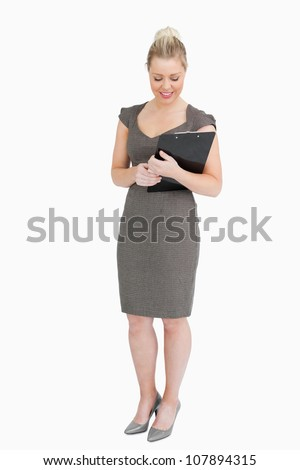 Businesswoman looking at notepad in her hands against white background - stock photo
