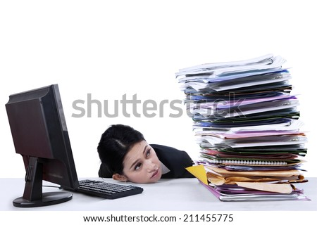 Businesswoman looking at pile of documents on the desk - stock photo