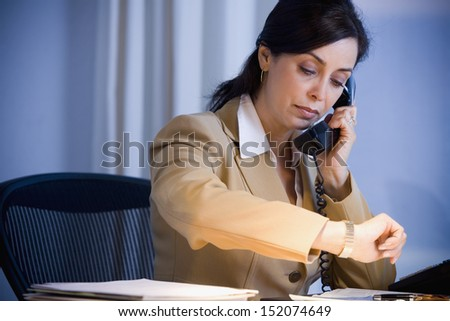 Businesswoman looking at watch - stock photo