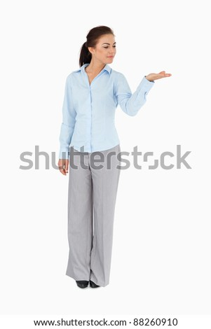 Businesswoman looking at what she is presenting against a white background - stock photo