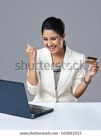 Businesswoman looking excited while doing online shopping on a laptop