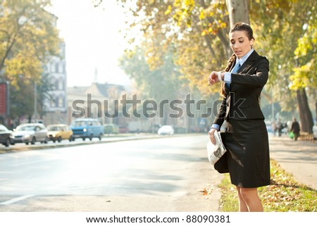 businesswoman looking in watch,  late for work or a meeting - stock photo