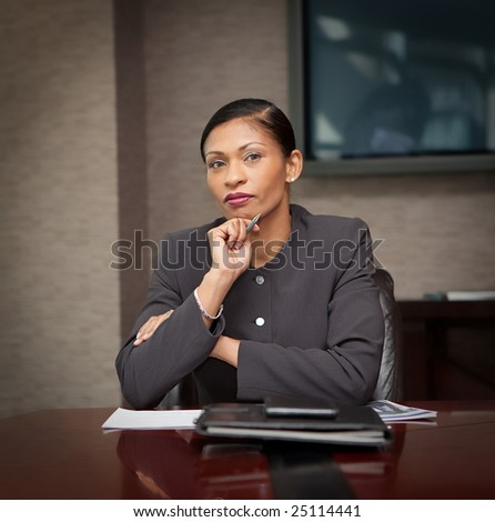 Businesswoman looking into camera, holding pen - stock photo