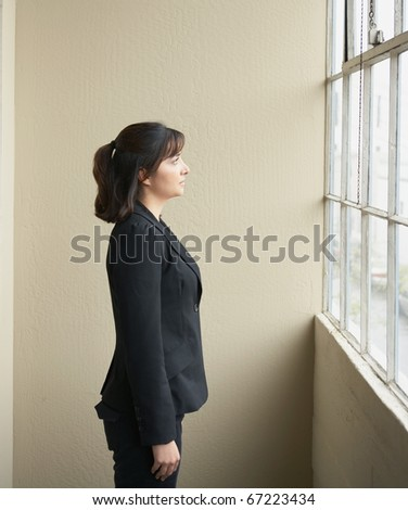 Businesswoman looking out window - stock photo